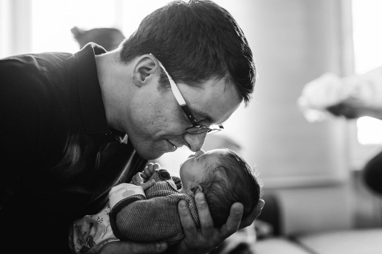 Papa hält kleines Baby in den Händen, die Nasenspitzen berühren sich