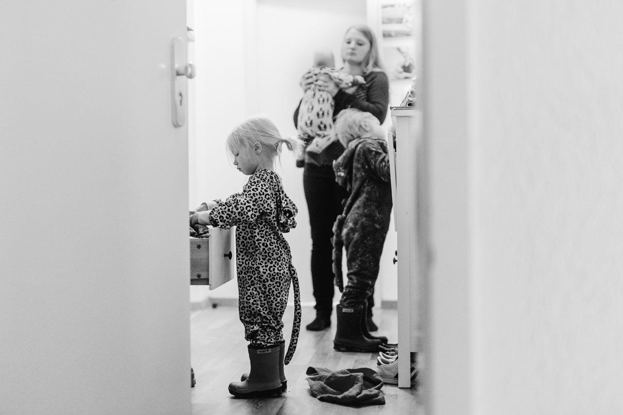 Kleines Mädchen sucht in der Schublade , im Hintergrund hält ihre Mutter das baby auf dem Arm