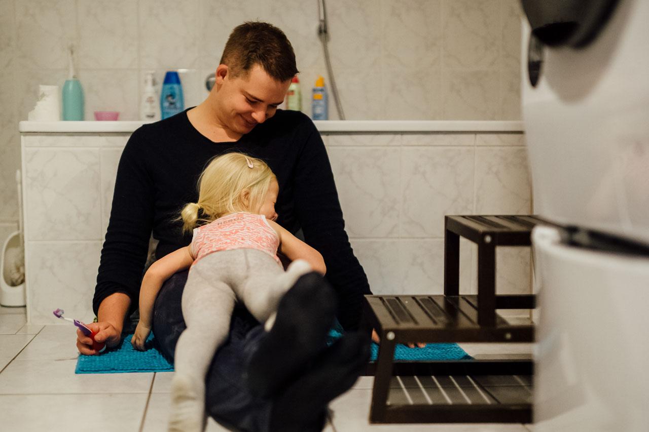 Tochter liegt auf den Beinen des Vaters , der an der Badewanne lehnt