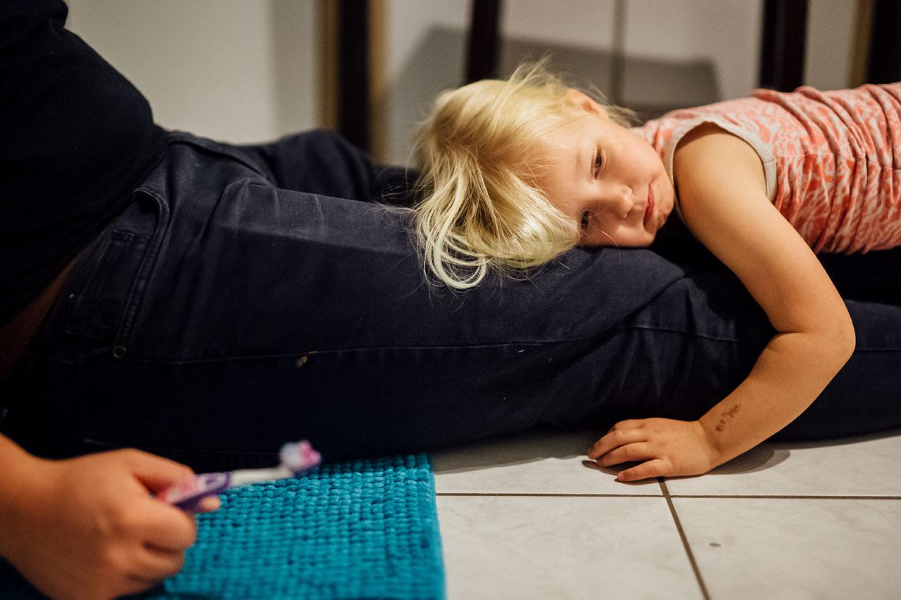 Kind liegt erschöpft auf den Beinen des Vaters