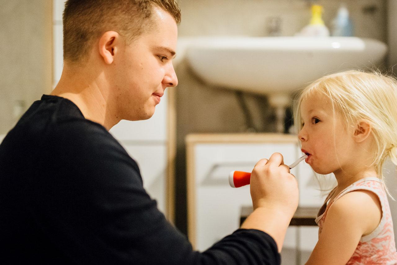 Vater hilft seiner Tochter beim Zähne Putzen