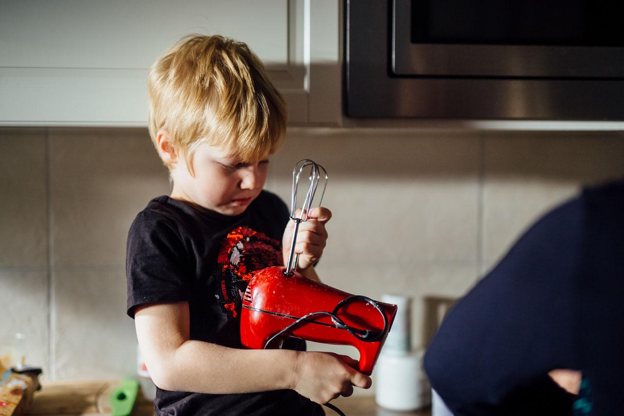 Kleiner Junge versucht die Stäbe vom Rührgerät zu lösen