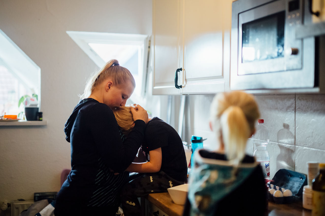 Mutter und ihre Kinder in der Küche , Mutter küsst ihren Sohn auf den Kopf