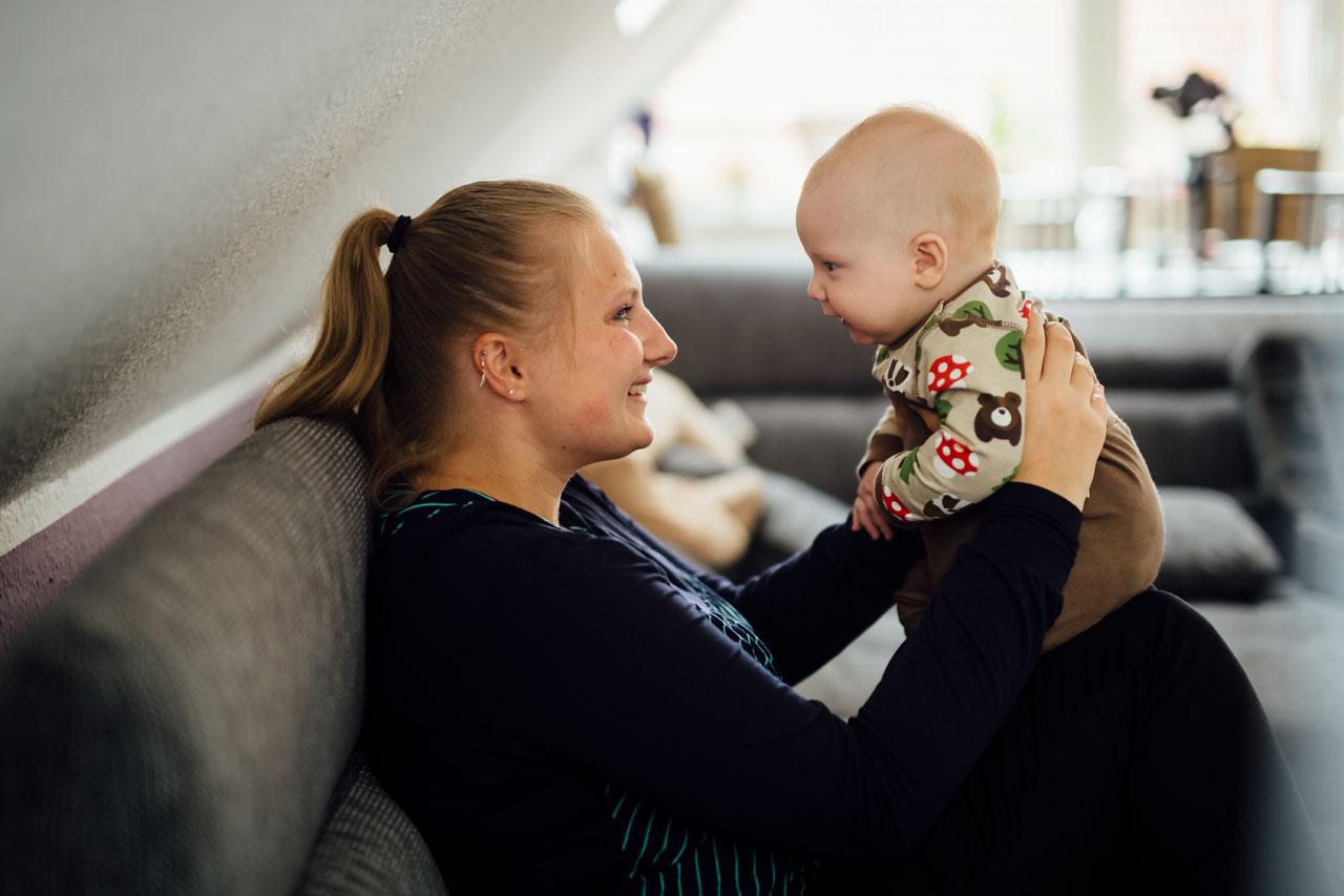 Mutter hebt ihr Baby auf ihre Knie