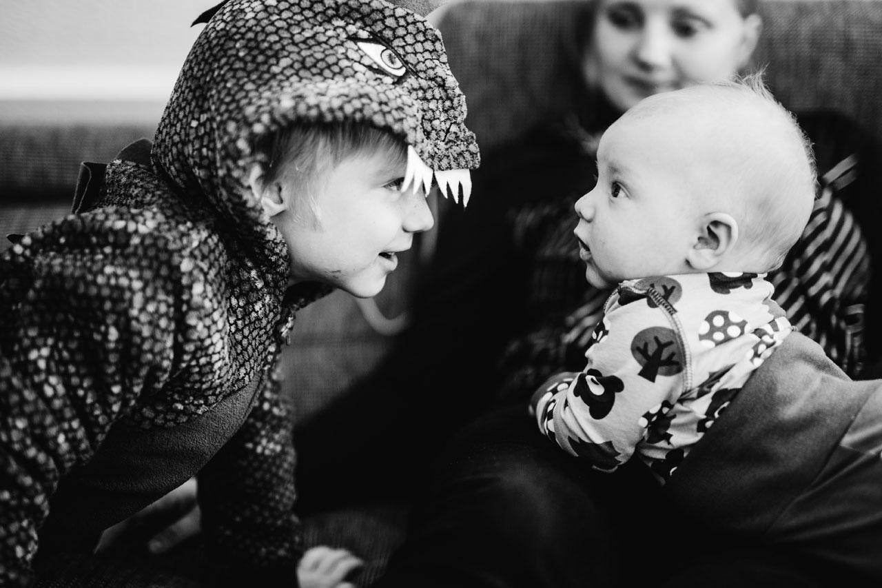 Zwei Kinder und ihre Mutter , Baby schaut sein Bruder an , der ein Kostüm trägt
