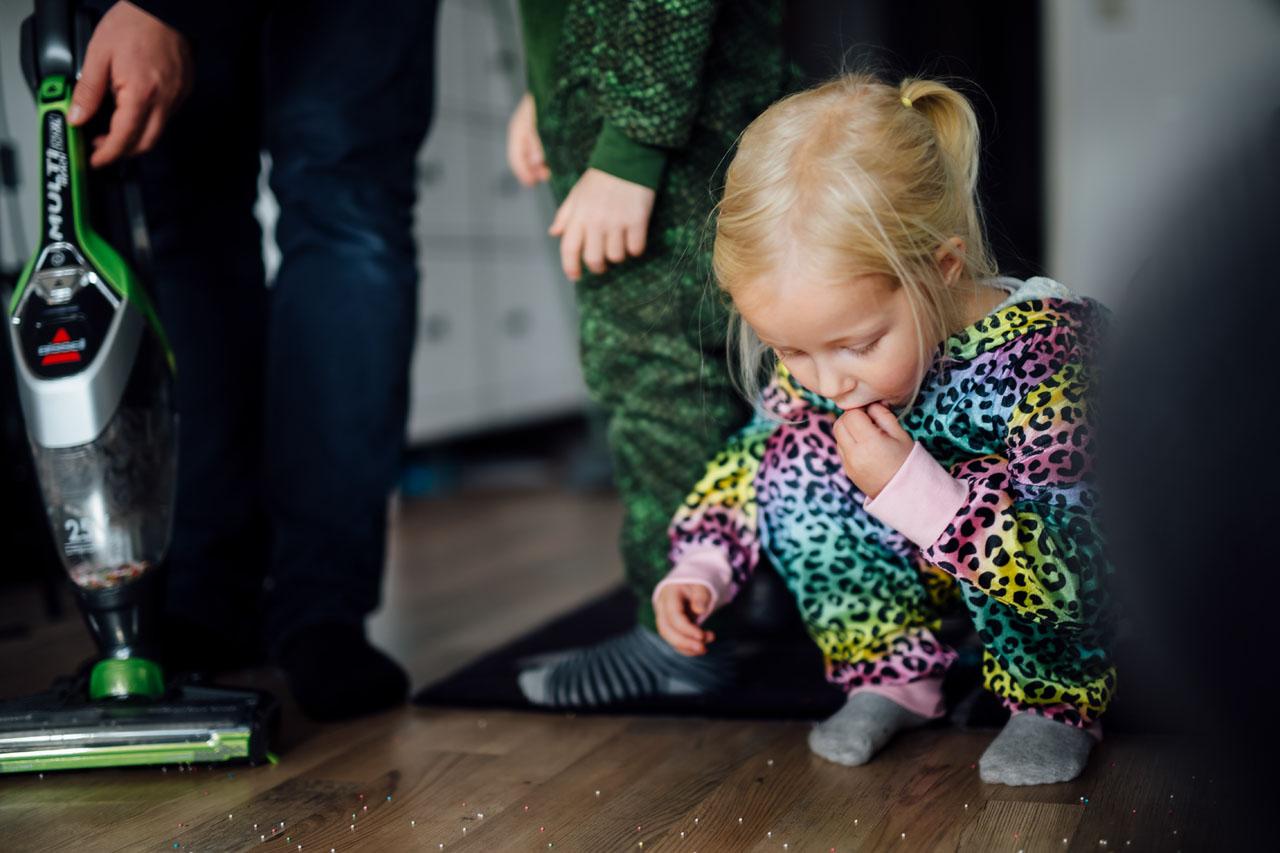 Kleines Mädchen isst die Zuckerperlen , die auf dem Boden liegen