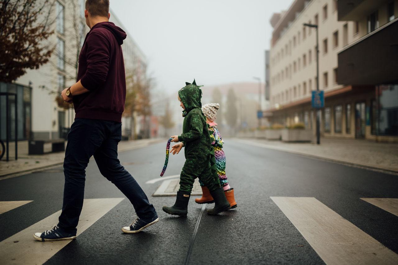 Vater und seine zwei Kinder im Kostüm gehen über den Zebrastreifen
