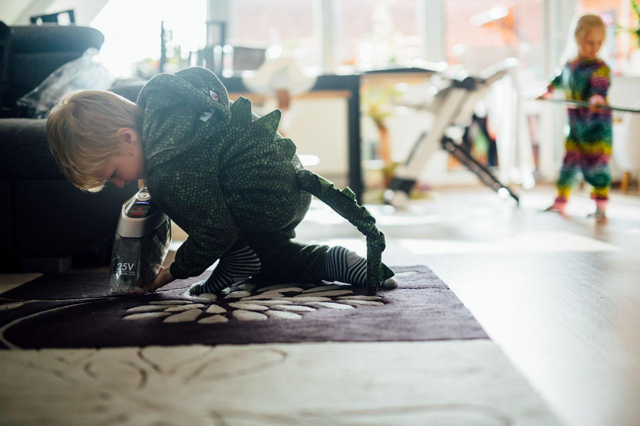 kleiner Junge im Kostüm staubsaugt den Teppich