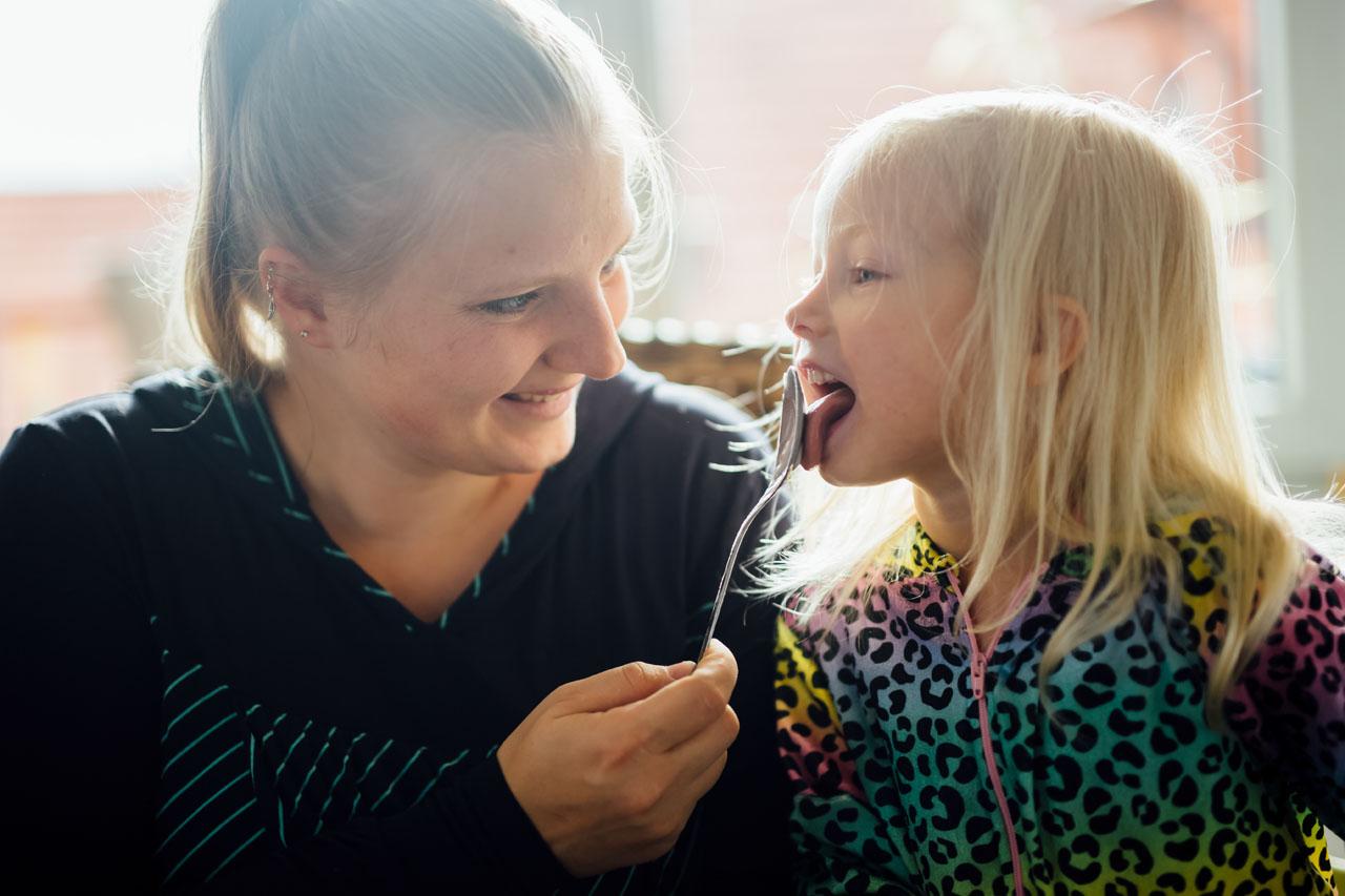 Kind leckt den Löffel ab , den die Mutter in der Hand hält