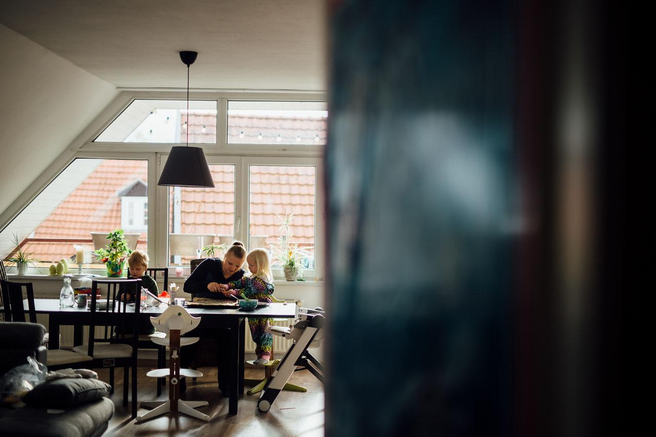 Mutter und zwei Kinder sitzen am Tisch