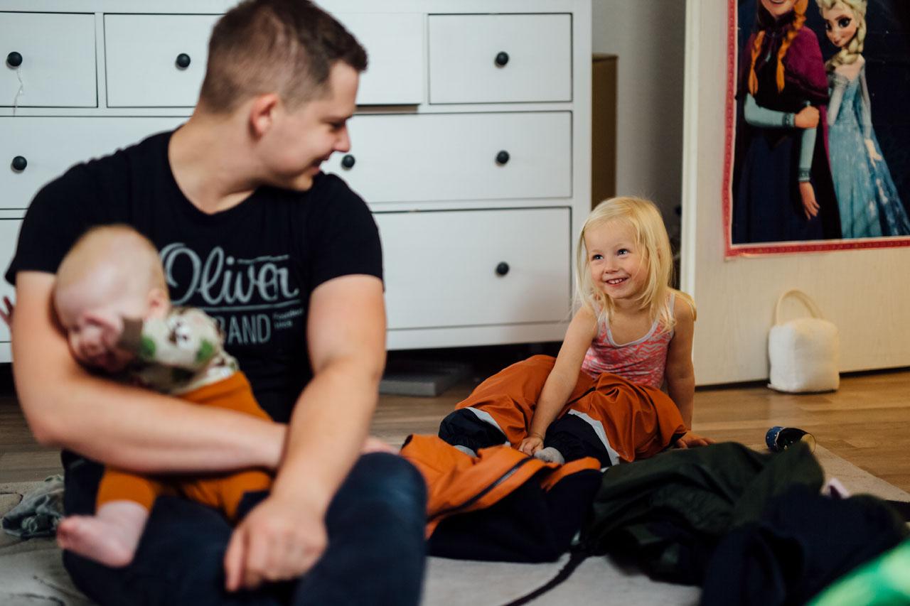 Vater und seine zwei Kinder sitzen auf dem Teppich , Tochter und Vater lachen sich an