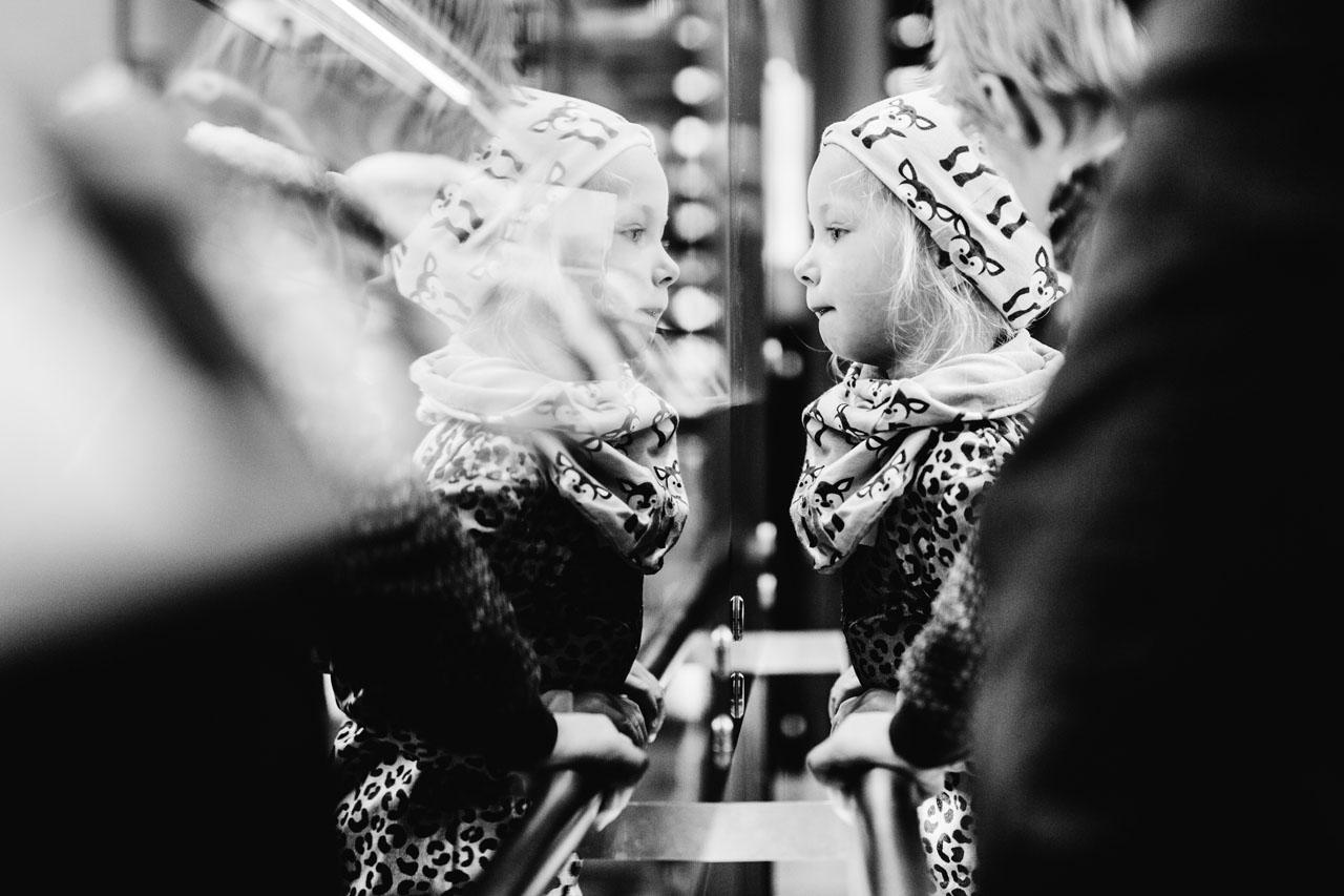 Kleines Mädchen schaut sich im Spiegel an