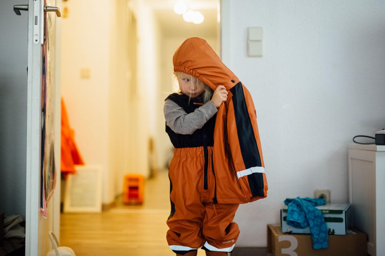 Kind zieht seine Jacke an