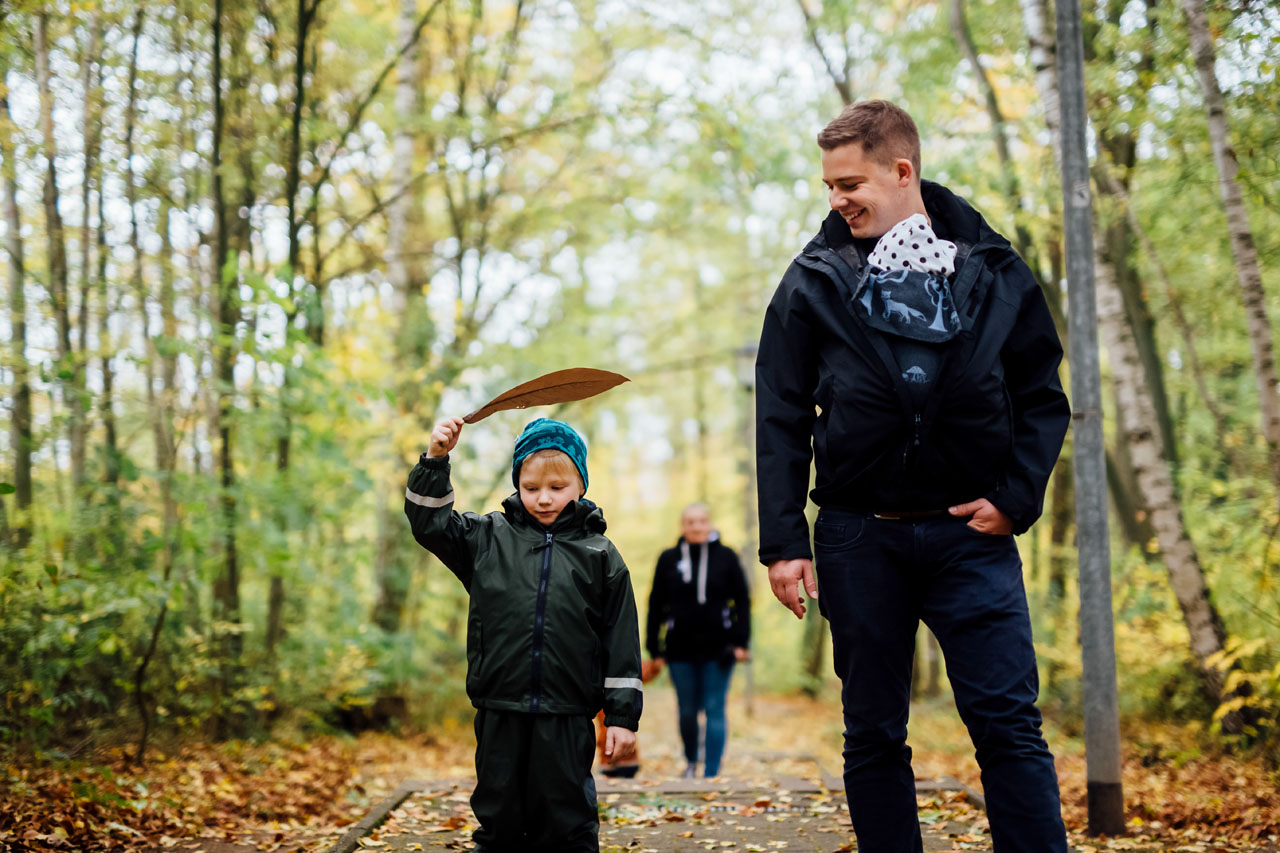 Familie im Wald, Sohn hält Laubblatt hoch