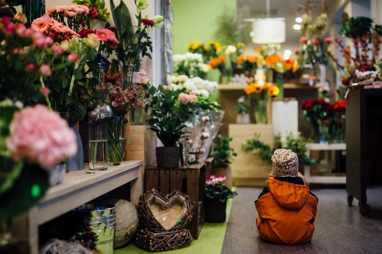 Kind sitzt im Blumenladen