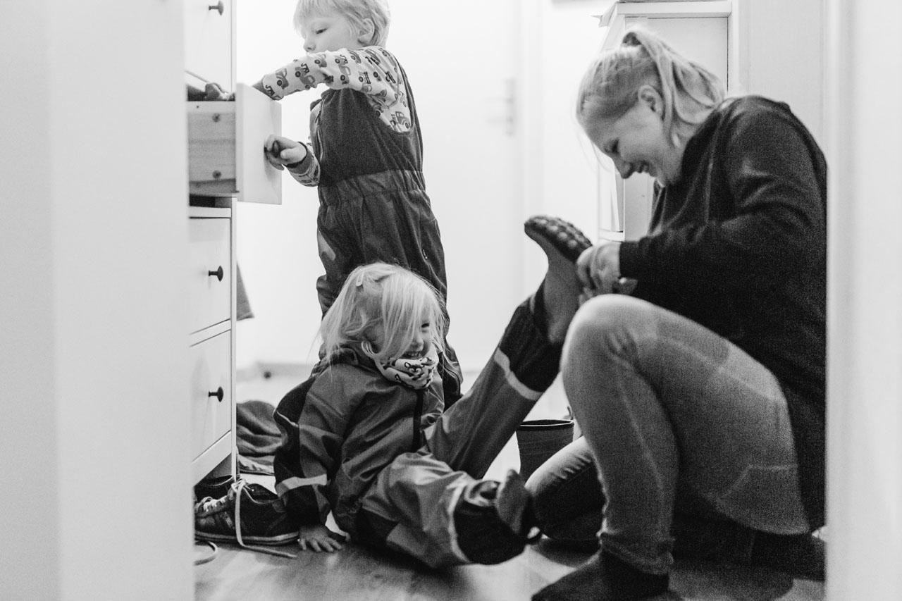Mutter hilft ihrer Tochter beim Schuhe anziehen während der Sohn in der Schublade kramt