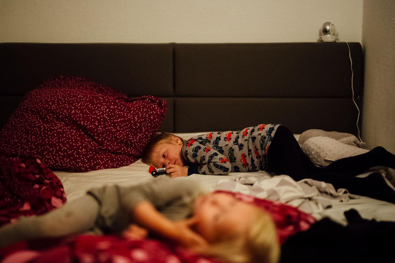Kind liegt erschöpft auf dem Bett mit einem Spielzeugauto in der Hand