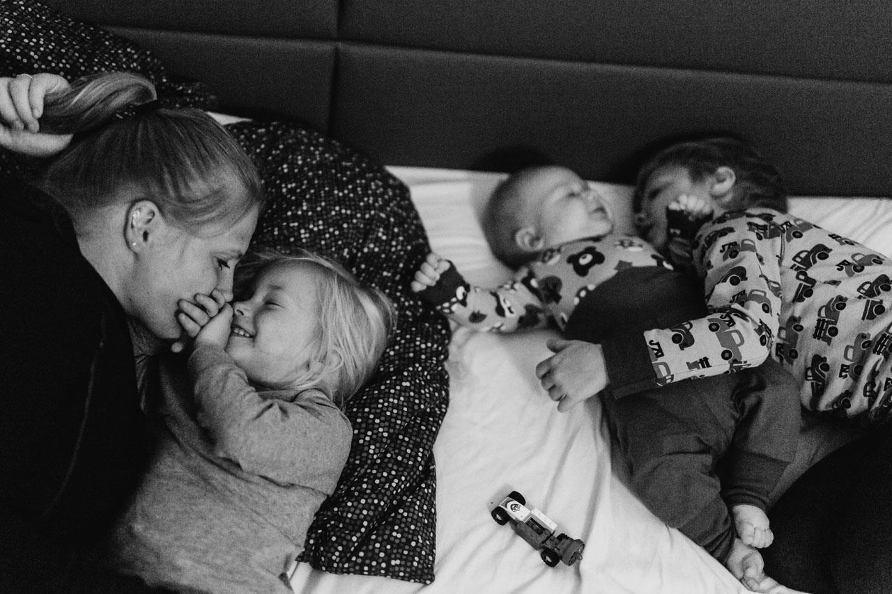 Mutter und drei Kinder liegen im Bett