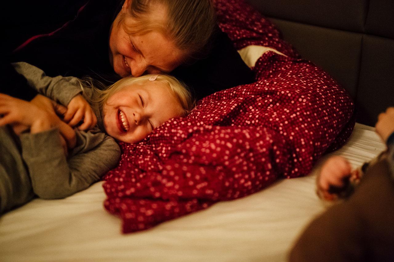 Mutter und Tochter lachend im Bett
