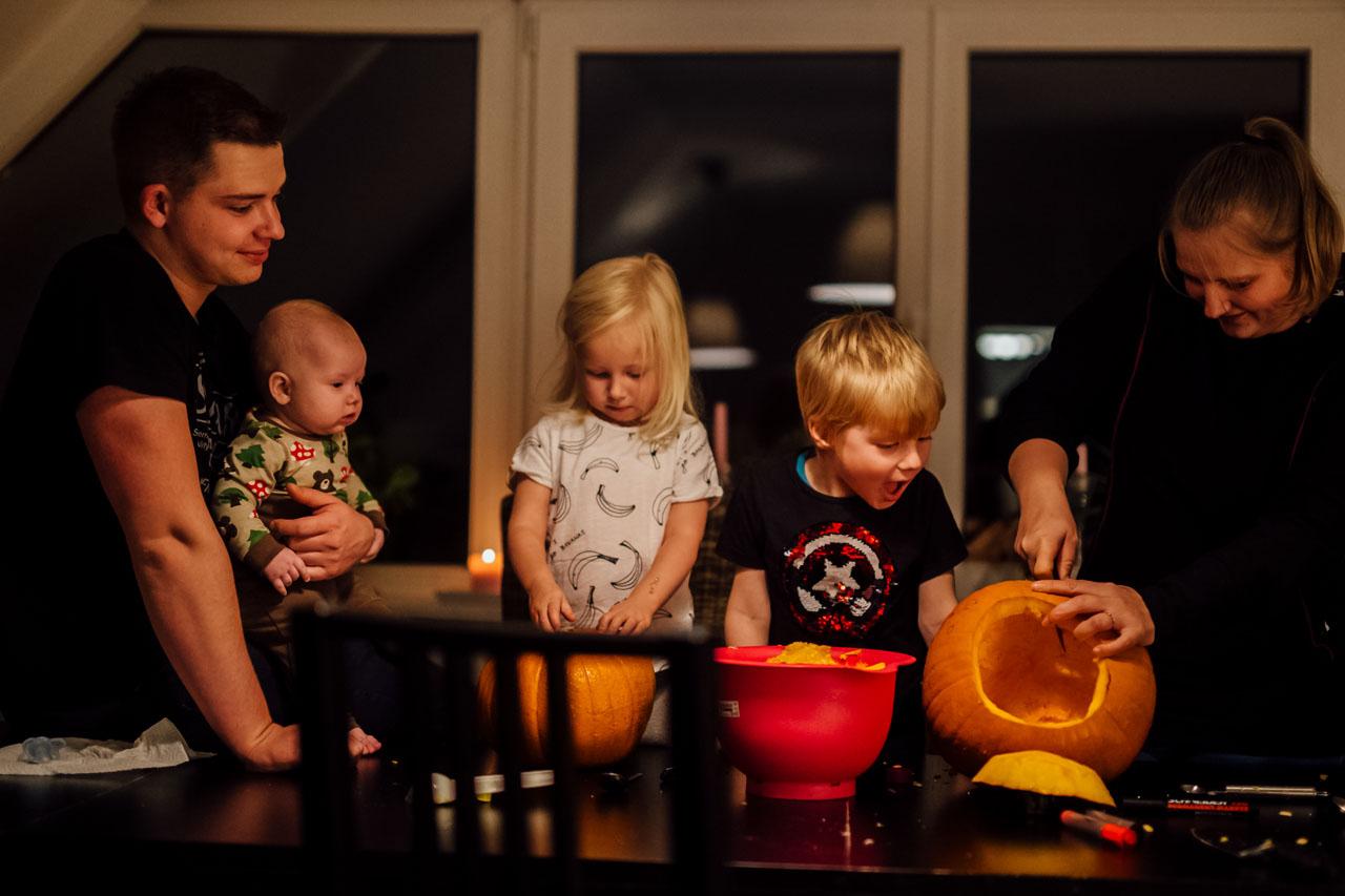 Familie mit drei Kindern schnitzen Kürbisse