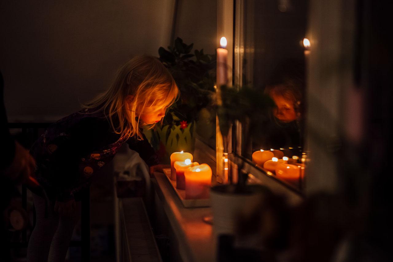Kind schaut brennende Kerzen an
