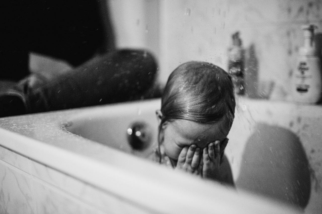Kind hält sich die Augen zu während es in der Badewanne mit Wasser nassgespritzt wird