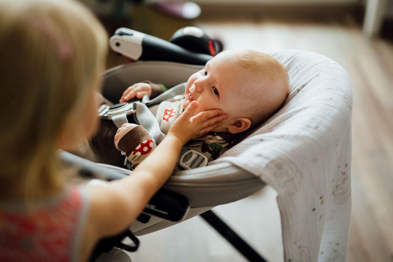 Schwester berührt das Baby im Gesicht