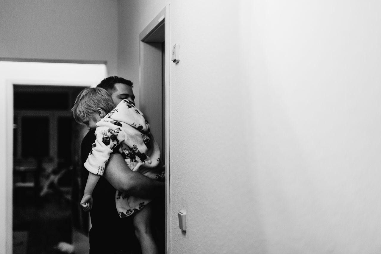 Vater trägt Kind ins Zimmer