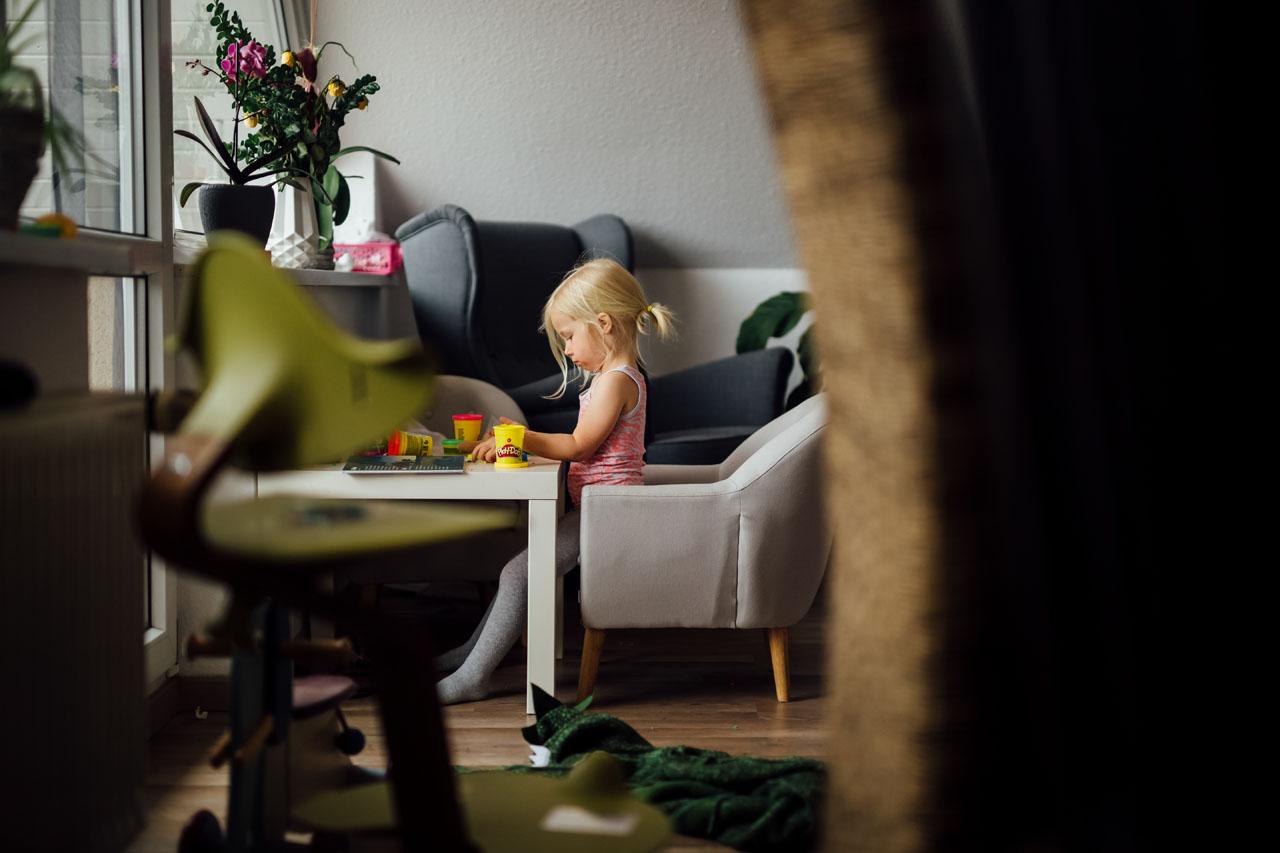 Kleines Mädchen sitzt am Tisch und spielt