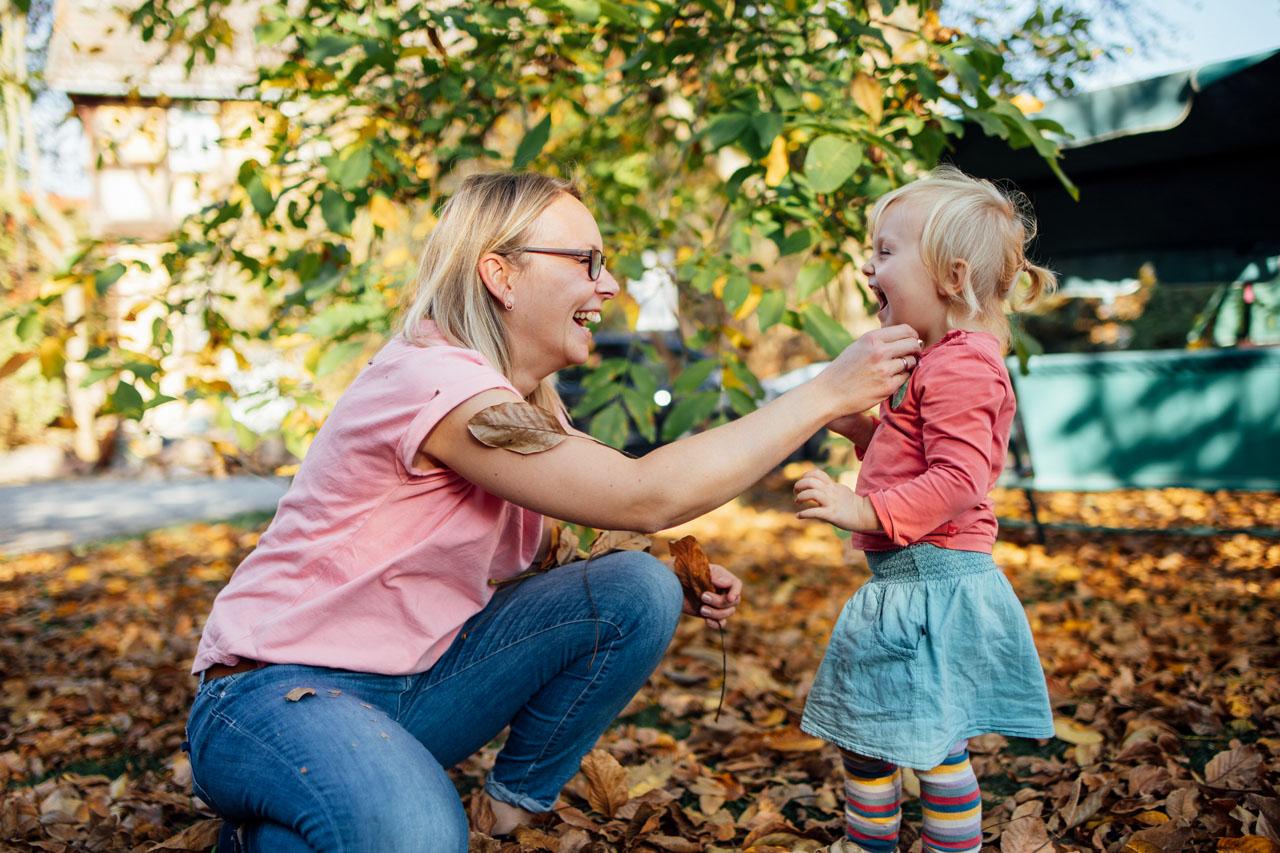 Mutter hockt und Tochter steht ihr gegenüber, sie lachen sich gegenseitig an