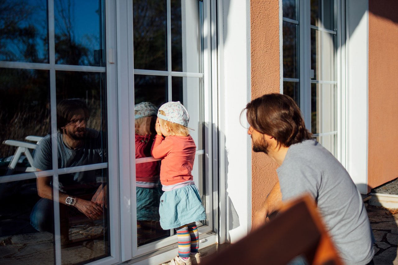 Mädchen steht dicht an einer Balkontür und schaut hindurch, Papa hockt hinter ihr