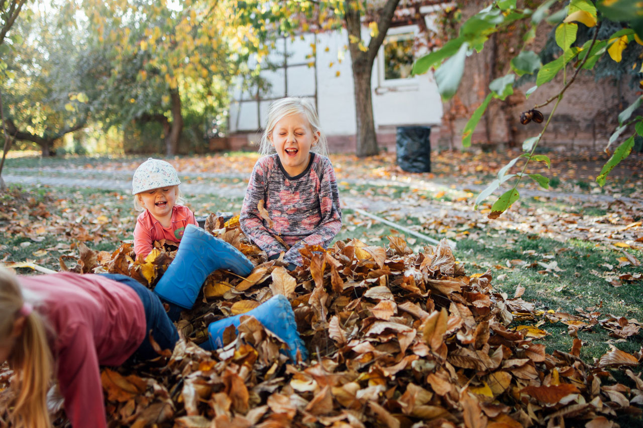 drei Mädchen sitzen im Laubhaufen
