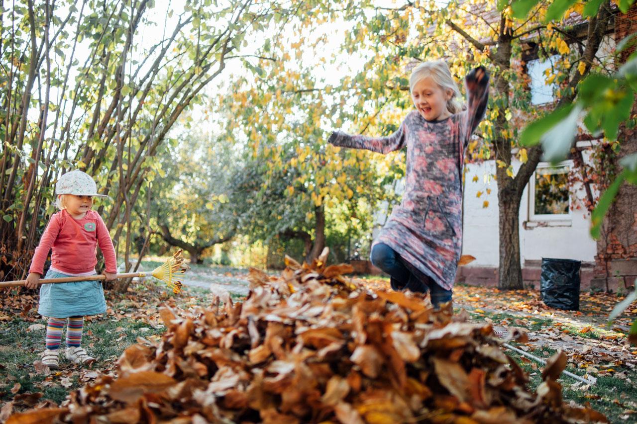 Mädchen springt in den Laubhaufen hinein, ihre Schwester steht daneben und beäugt die Sache kritisch