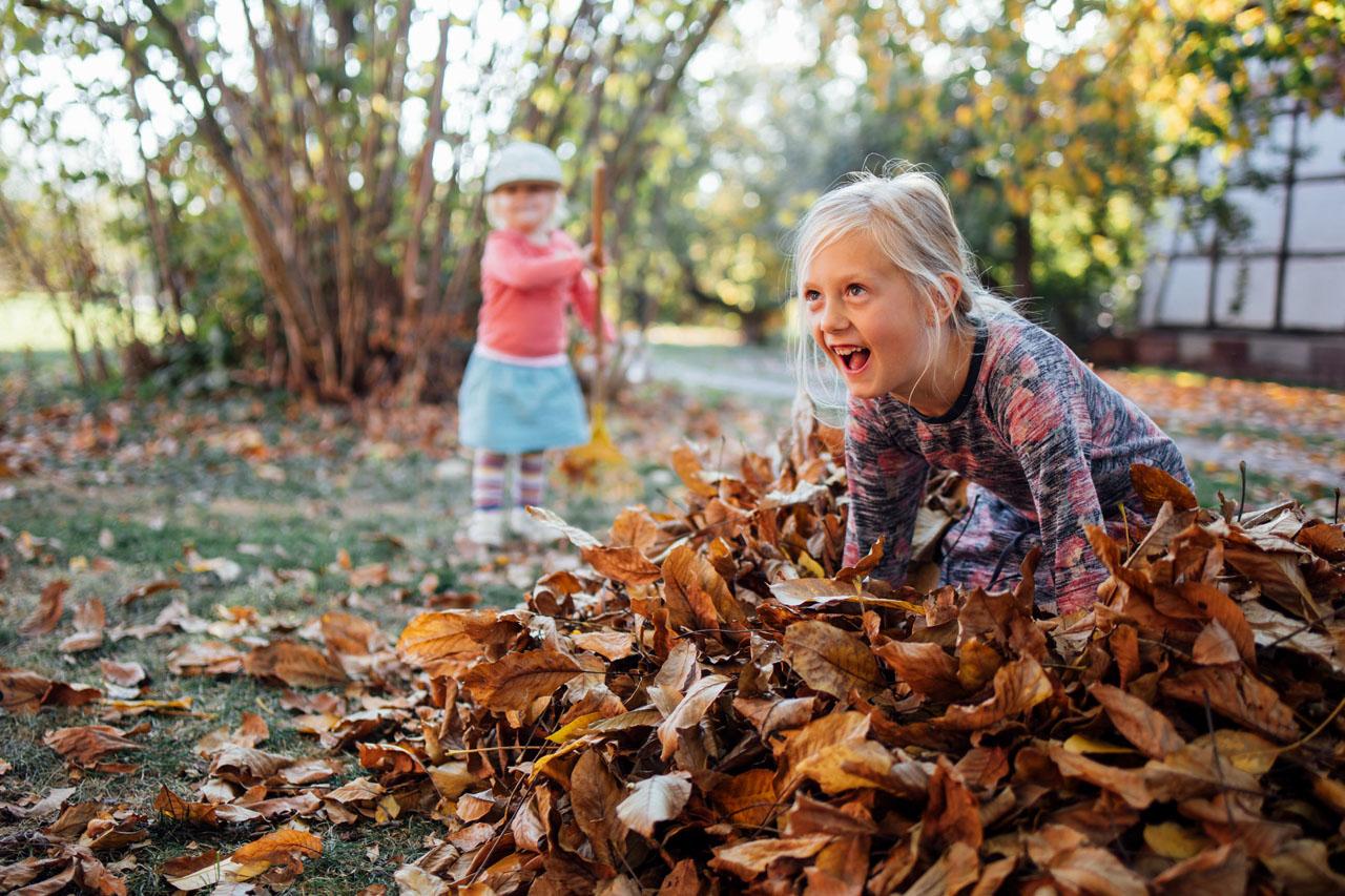 Mädchen sitzt im Laub mit vor Begeisterung geöffnetem Mund