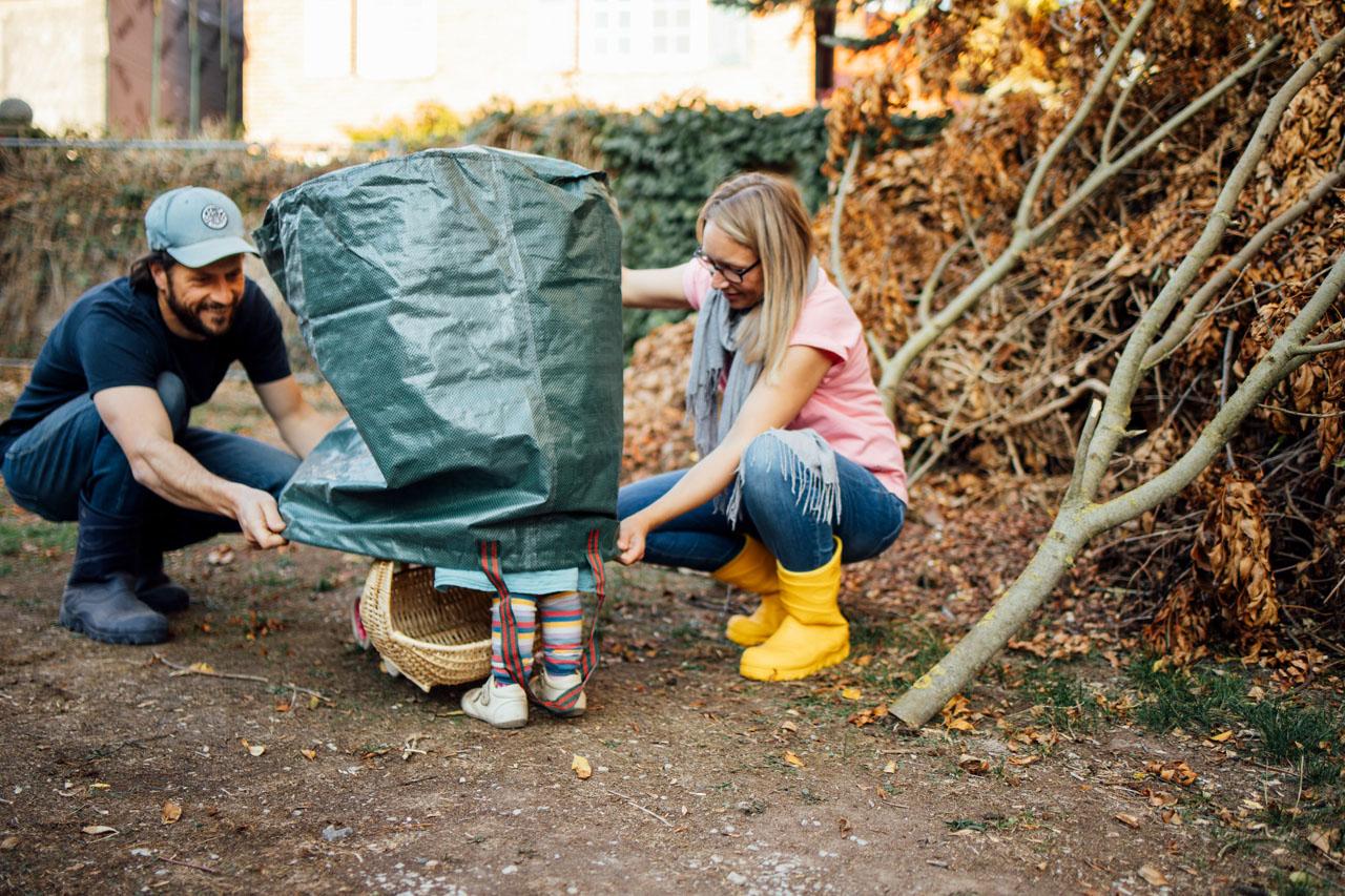 Eltern ziehen den Laubbeutel hoch, währenddessen sieht man Beine des Kindes auftauchen