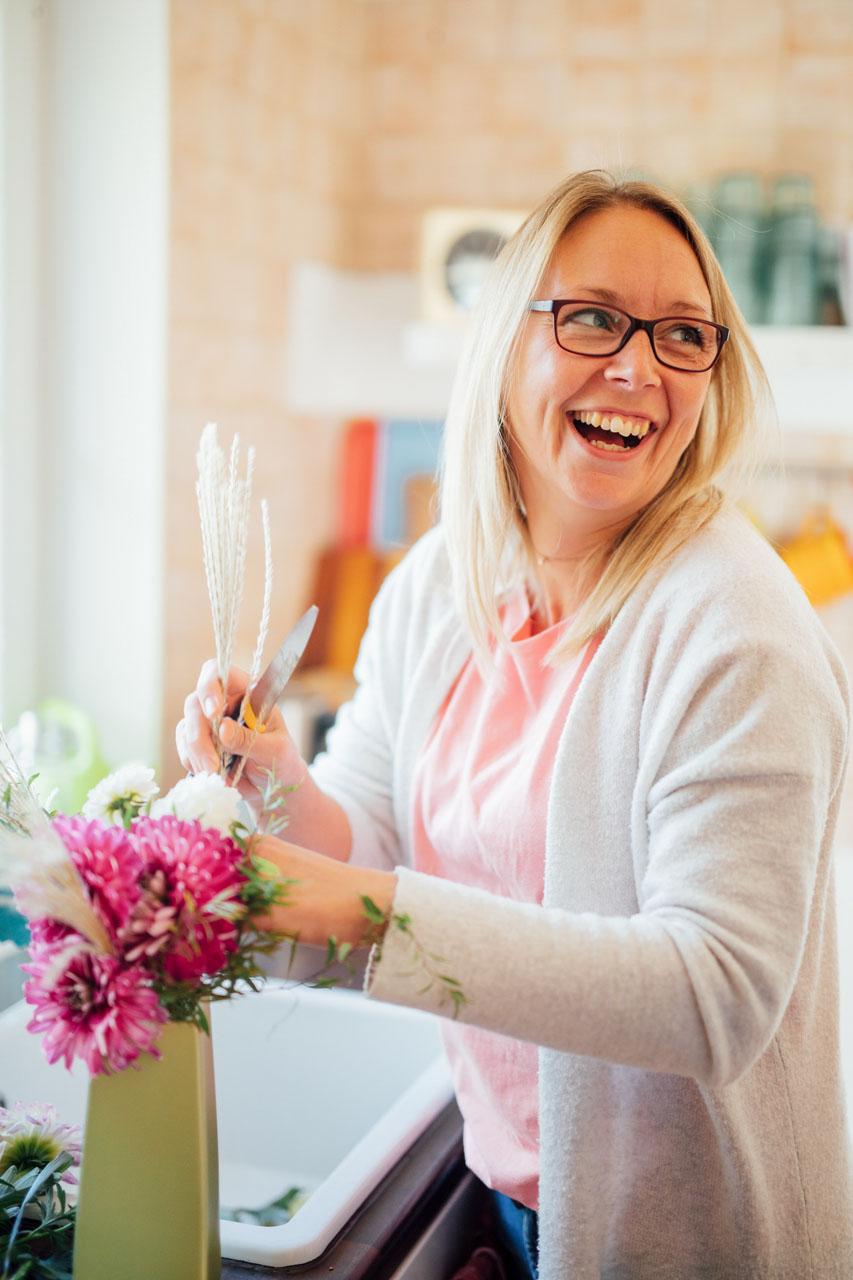 Mama bestückt eine Blumenvase und schaut dabei lachend über ihre Schulter