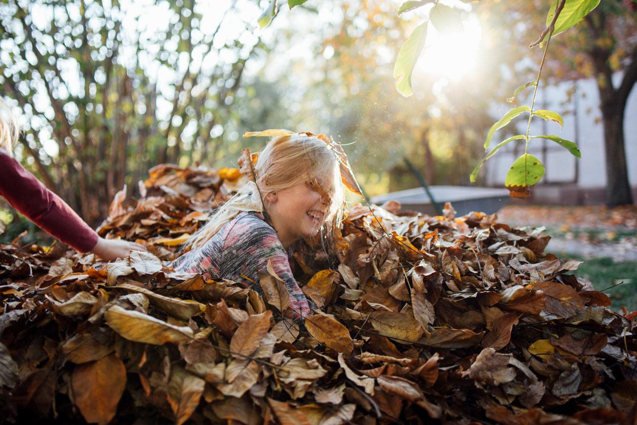 Mädchen liegt in einem Laubhaufen und lacht