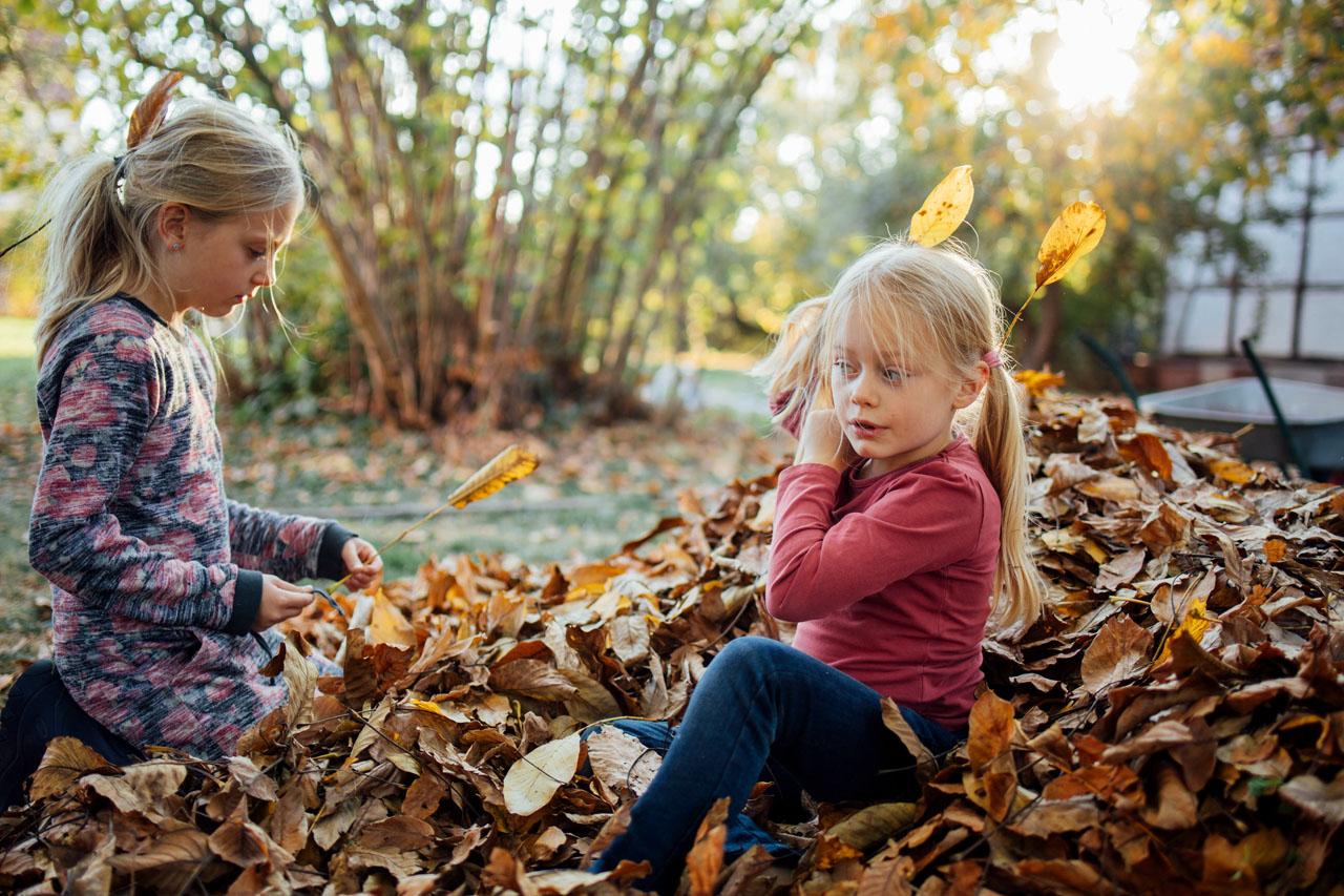 zwei Mädchen sitzen im Laub und stecken sich Blätter ins Haar