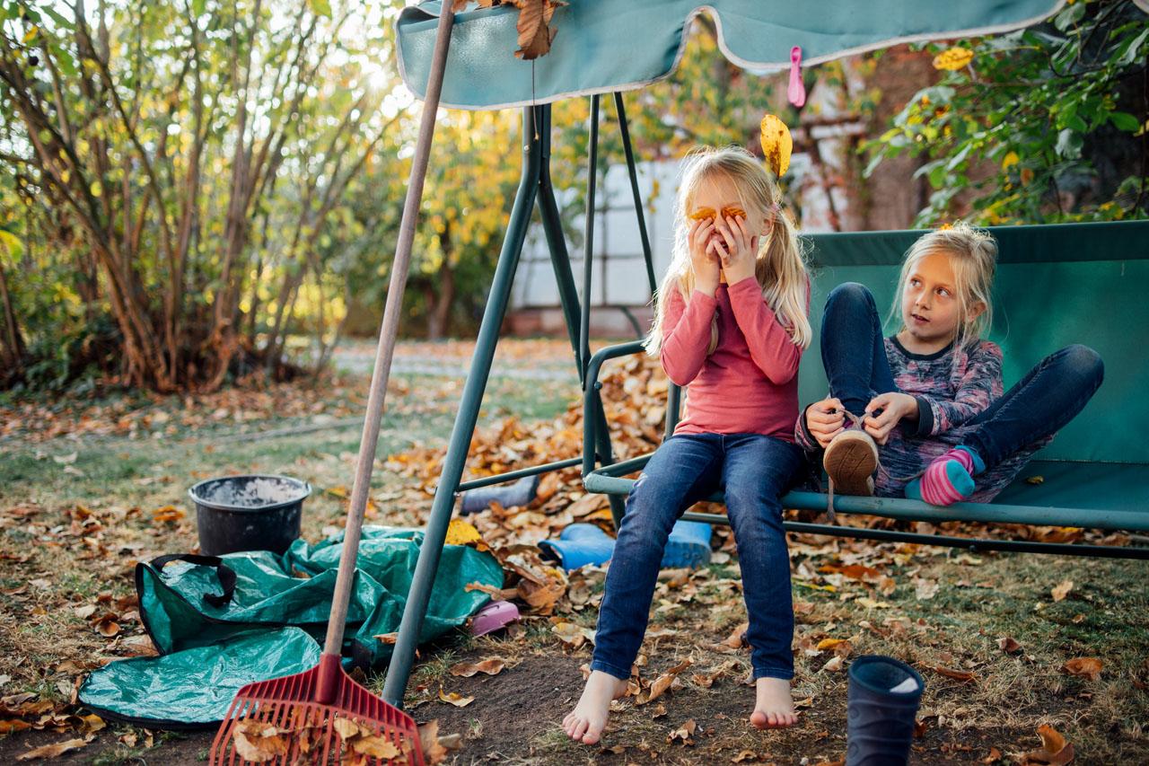 zwei Mädchen sitzen auf einer Hollywoodschaukel währenddessen das eine Mädchen sich zwei Blätter vor die Augen hält und das andere Mädchen die Schuhe bindet