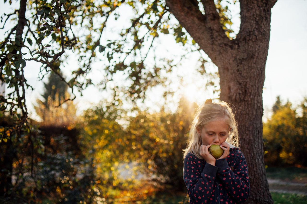 Mädchen beisst in eine Birne