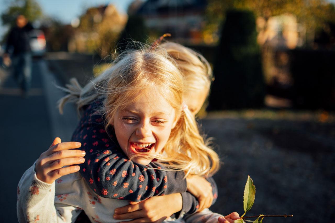 Mädchen umschlingt ein anderes Mädchen von hinten und lacht