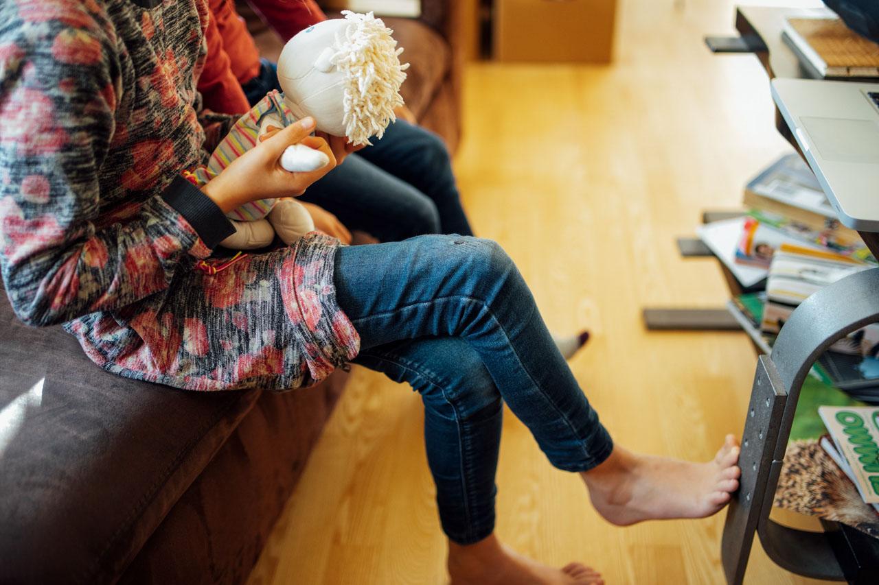 Mädchen sitzt mit überschlagenen Beinen auf der Couch und hat einen nackten Fuß gegen ein Tischbein gestützt