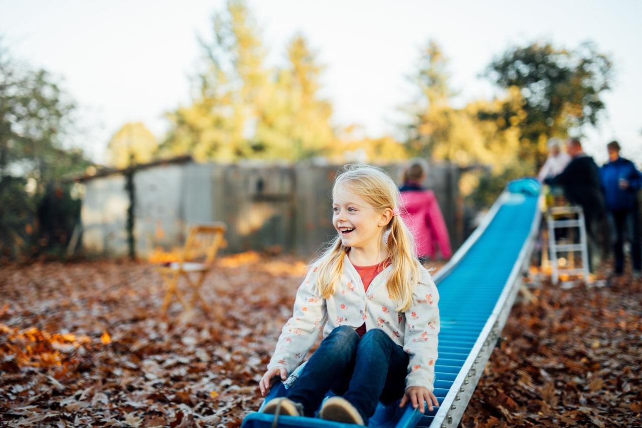 Kind lacht nach links und sitzt auf einen Schlitten