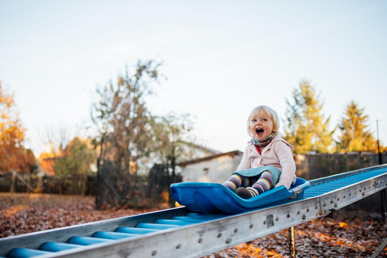 Kind sitzt auf einen Sommerschlitten auf Rollen und fährt
