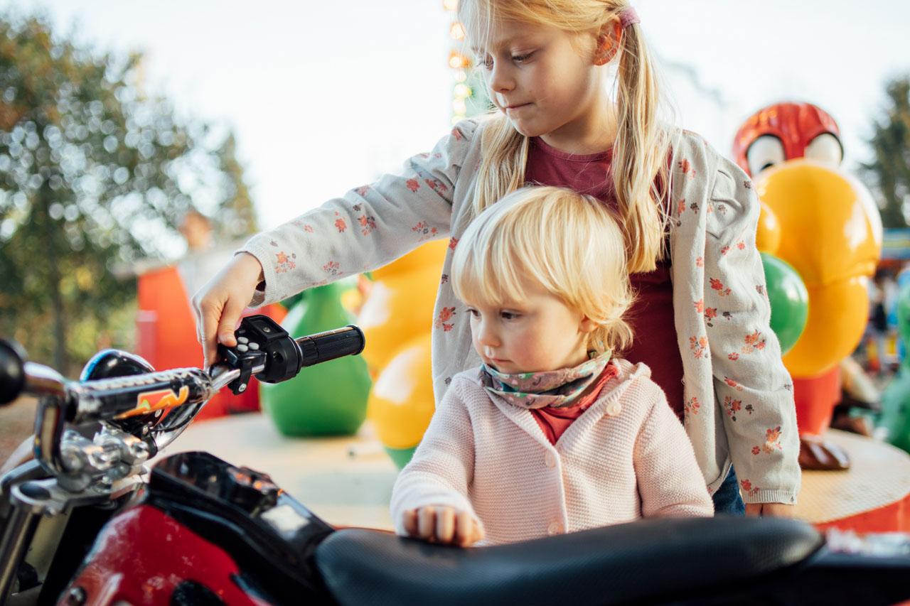 zwei Kinder schauen sich ein Kindermoped an
