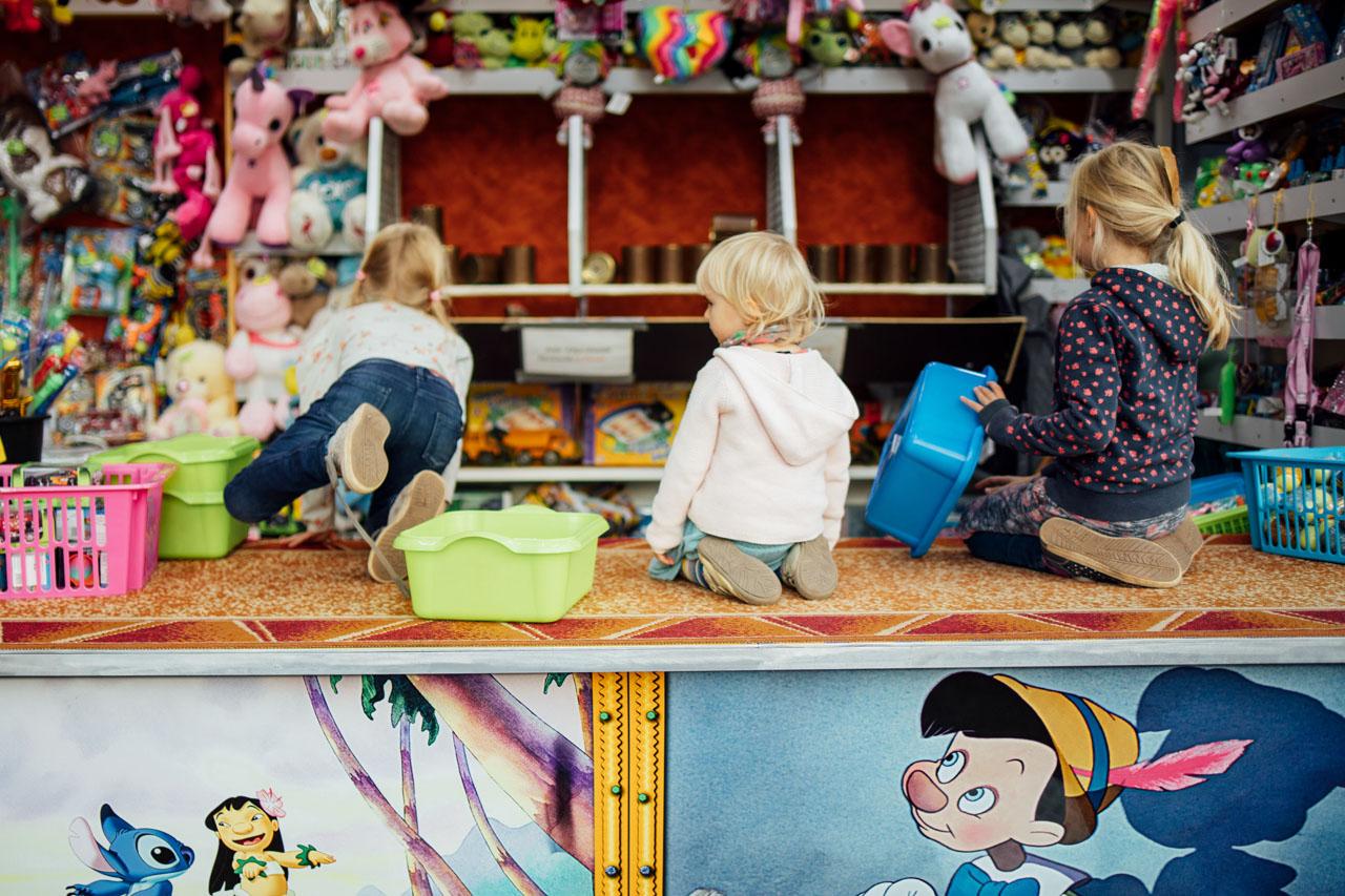 3 Kinder sitzen in der Hocke und schmeißen Blechdosen um