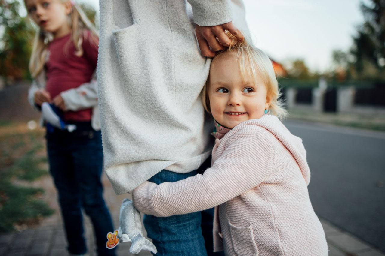 Kind umschlingt das Bein der Mutter
