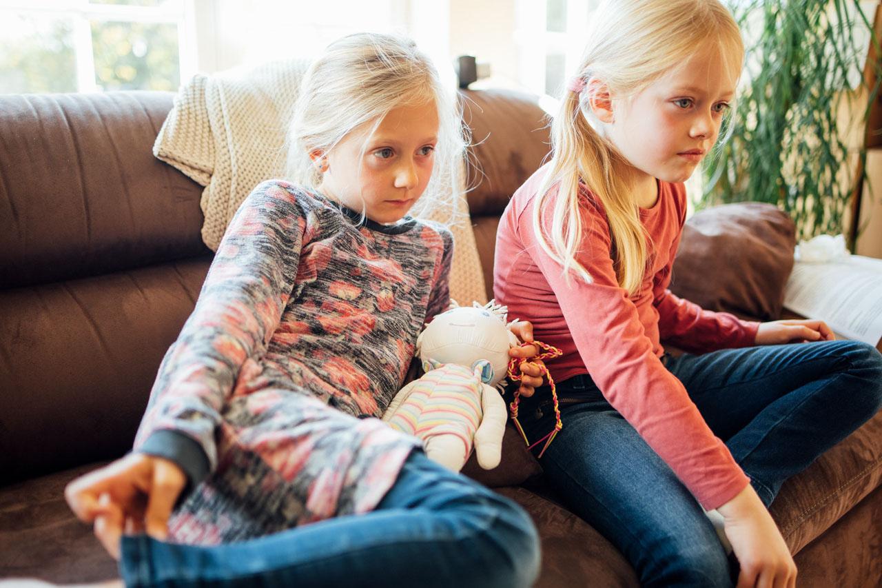 zwei Mädchen sitzen auf der Couch und schauen gebannt nach rechts