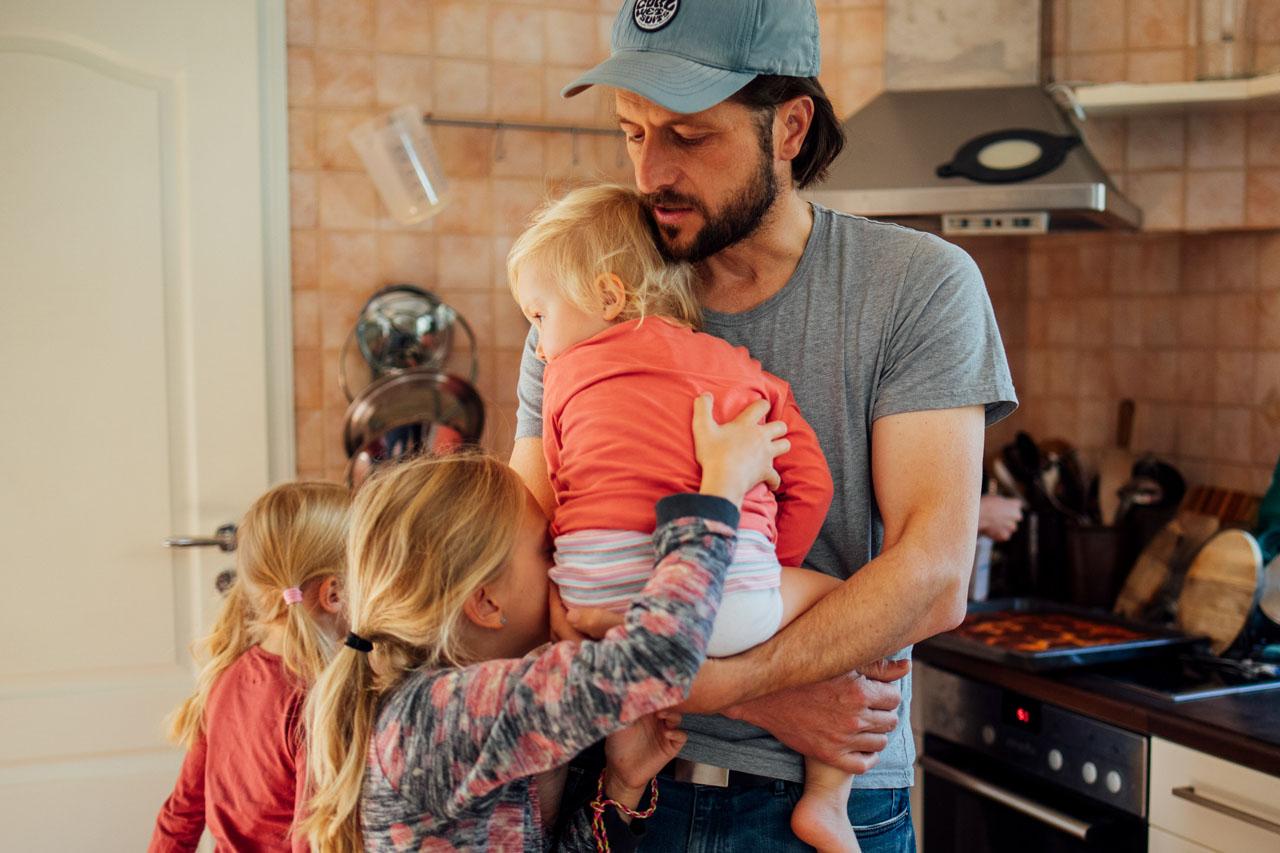Vater trägt kleinste Tochter vor dem Bauch, dabei kuscheln die beiden anderen Kinder mit ihm
