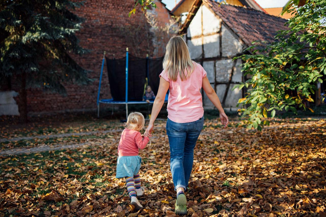 Mutter und Tochter laufen Hand in Hand im Garten rum